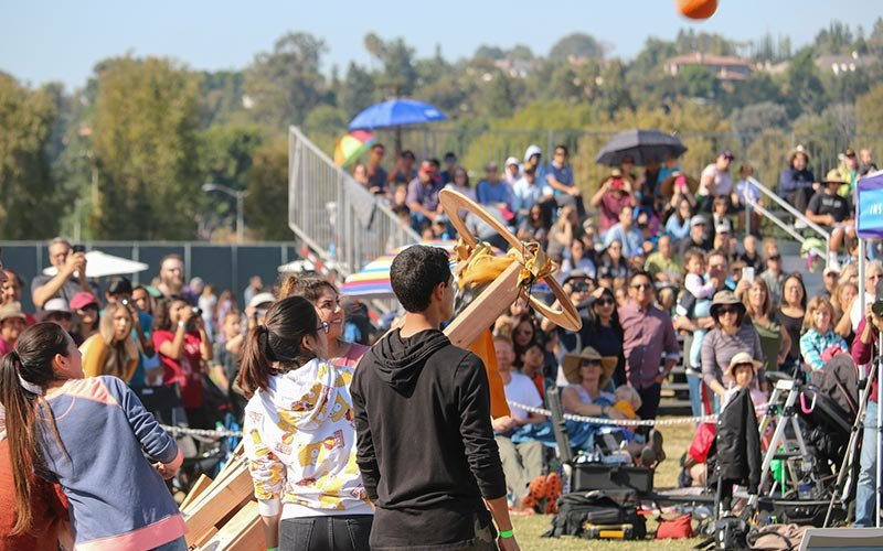 Students launching a pumpkin with custom made catapult.
