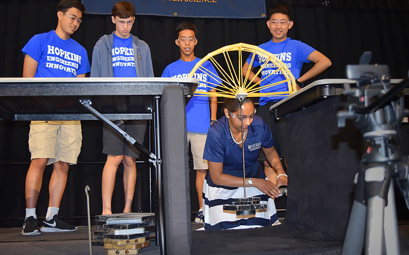 Beena Ajmera weighs a spaghetti bridge while students look on.
