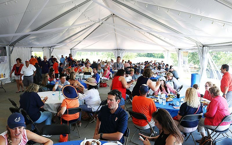 Titans team members and fans gather under tents enjoying barbecue.