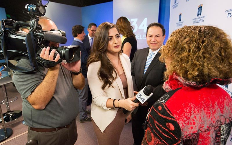 Univision reporter interviews President Mildred García during Dec. 15 festivities.
