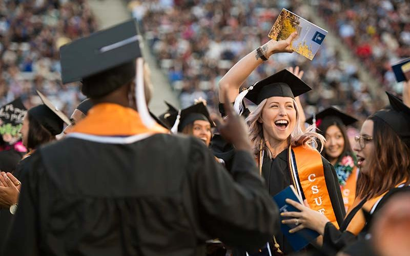 Happy graduate waves during Commencement 2018