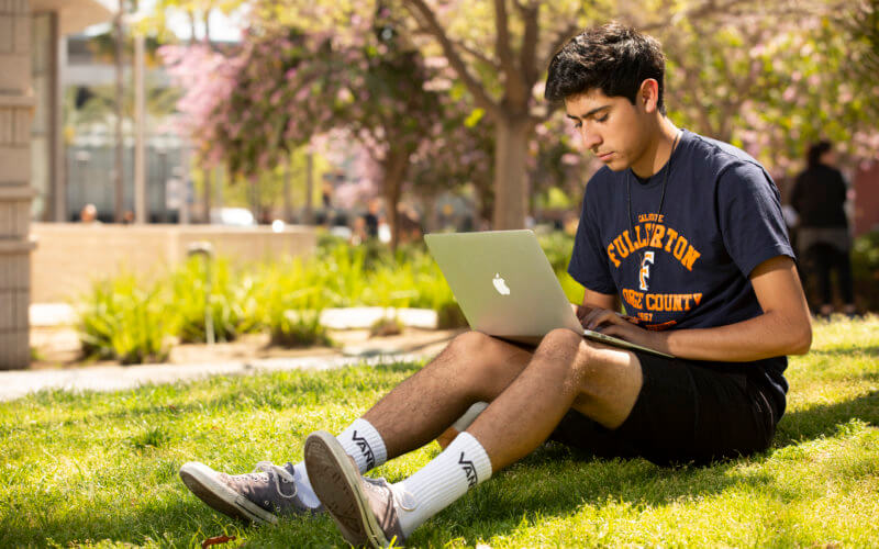 Student seated on grass working on laptop computer.