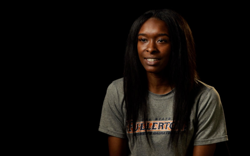 a Black woman smiling in a studio with a black background