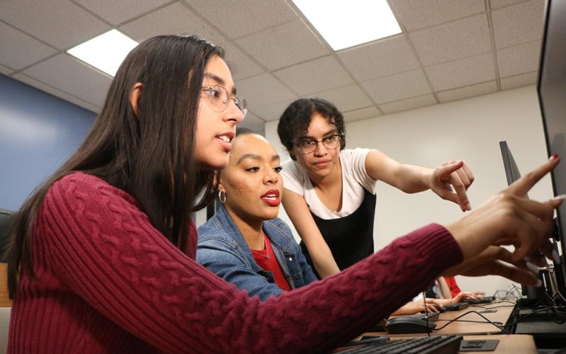 3 female students looking at computer screen