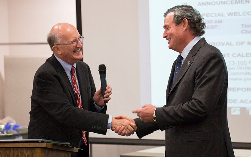 Bedell shaking hands with Chancellor White