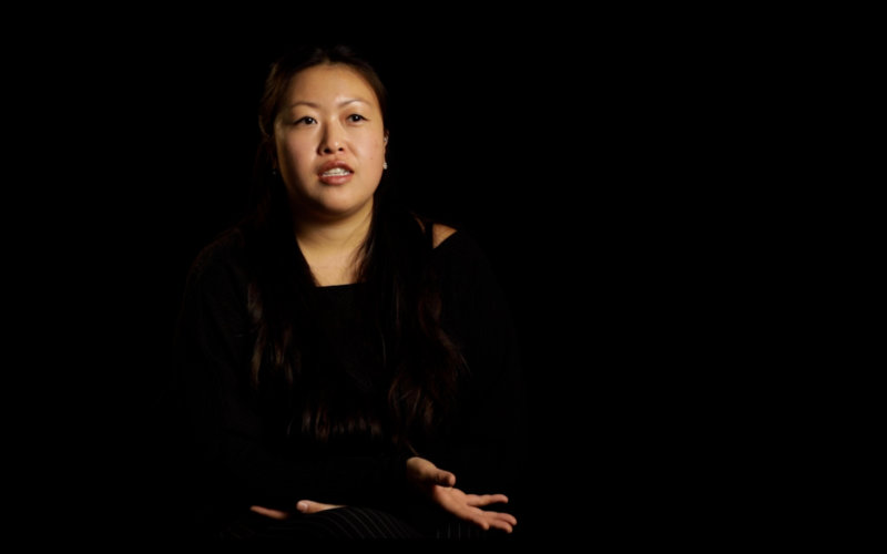 an Asian woman sitting and talking