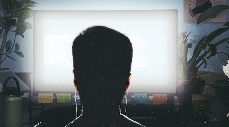 a man staring a glowing computer screen