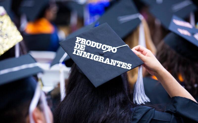 """Graduation cap that reads """"Producto de Inmigrantes"""""""