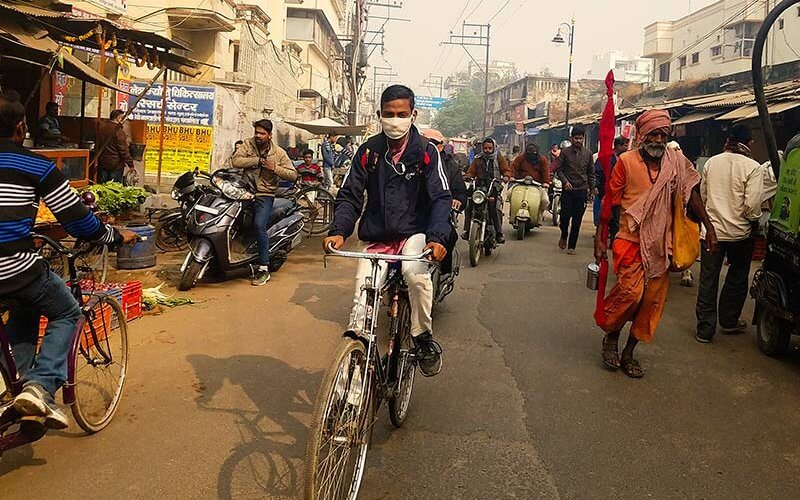 An idividual with a mask rides a bike through an Indian street with air pollution.