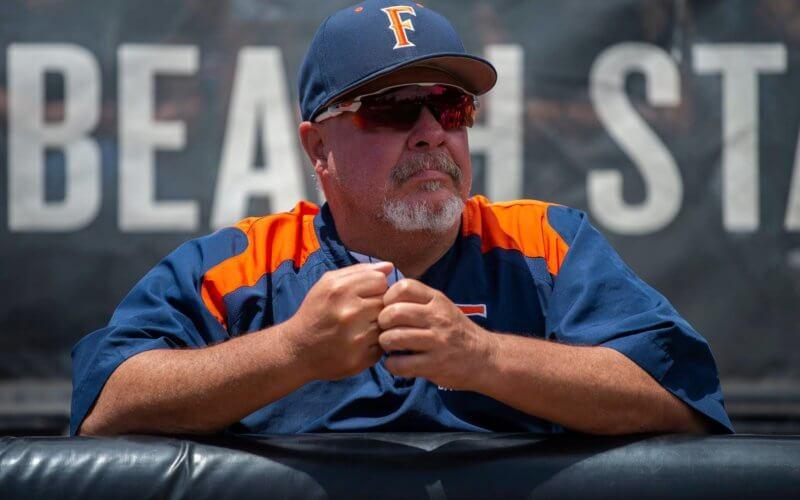 man wearing a baseball uniform, sunglasses and a baseball cap