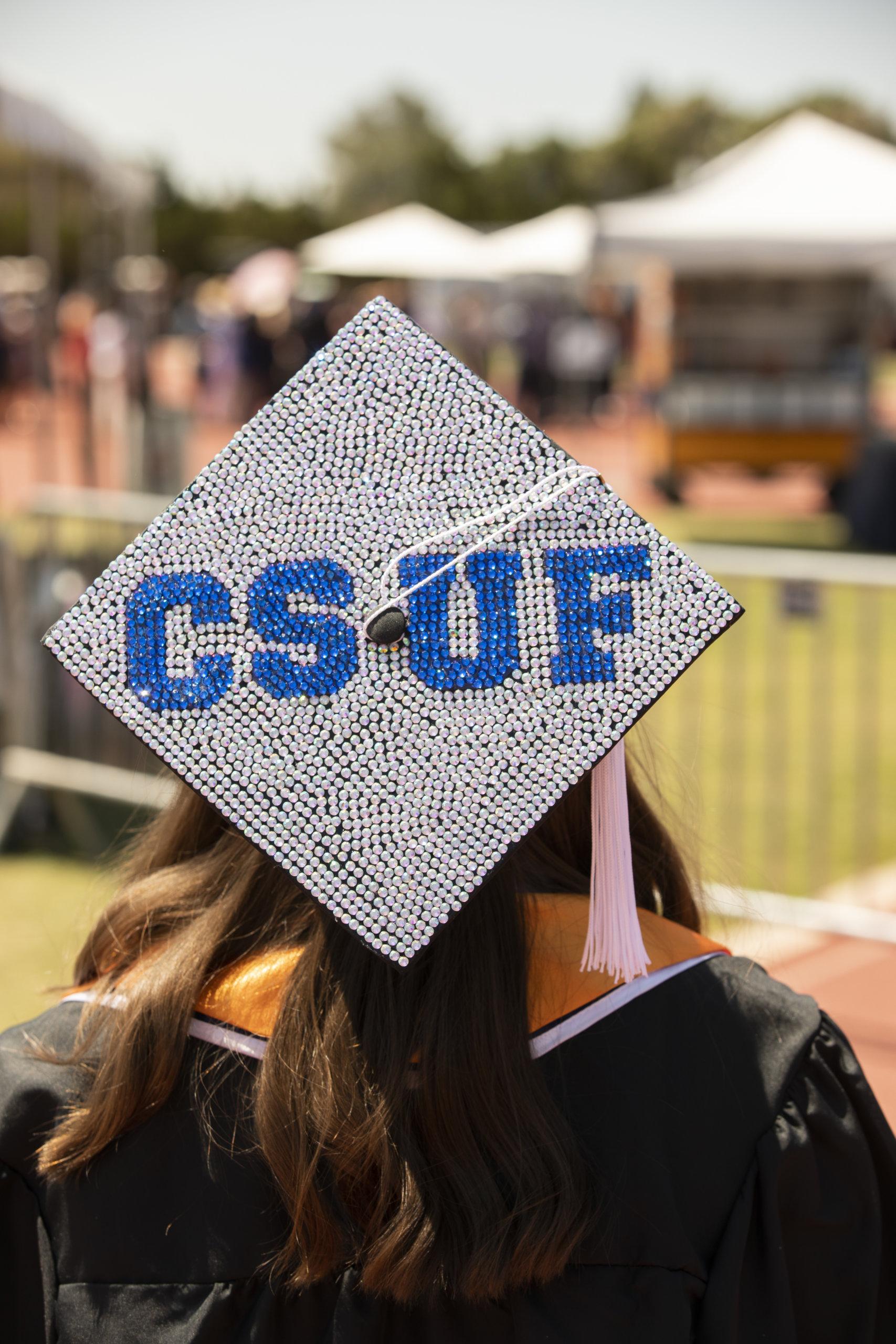 "Bedazzled grad cap reads ""CSUF"" in"