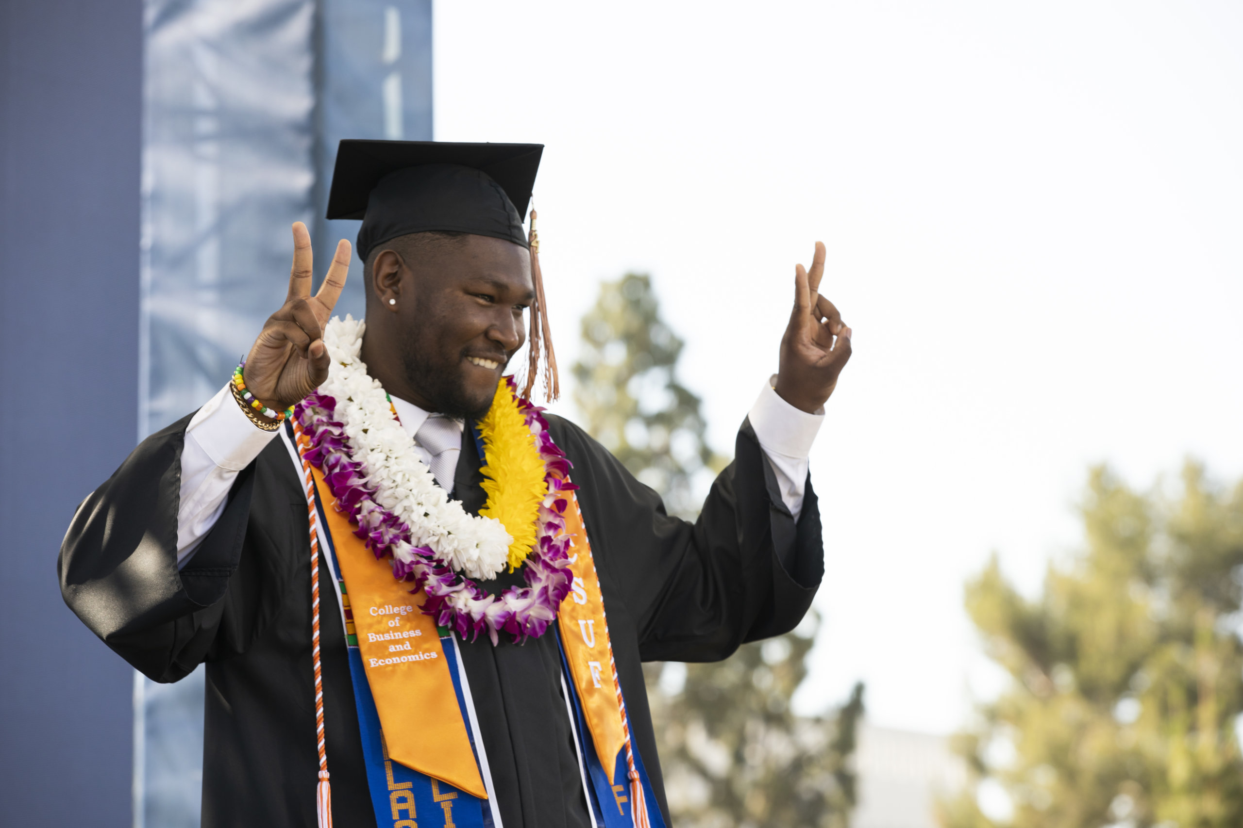 Happy graduate shows peace sign from stage