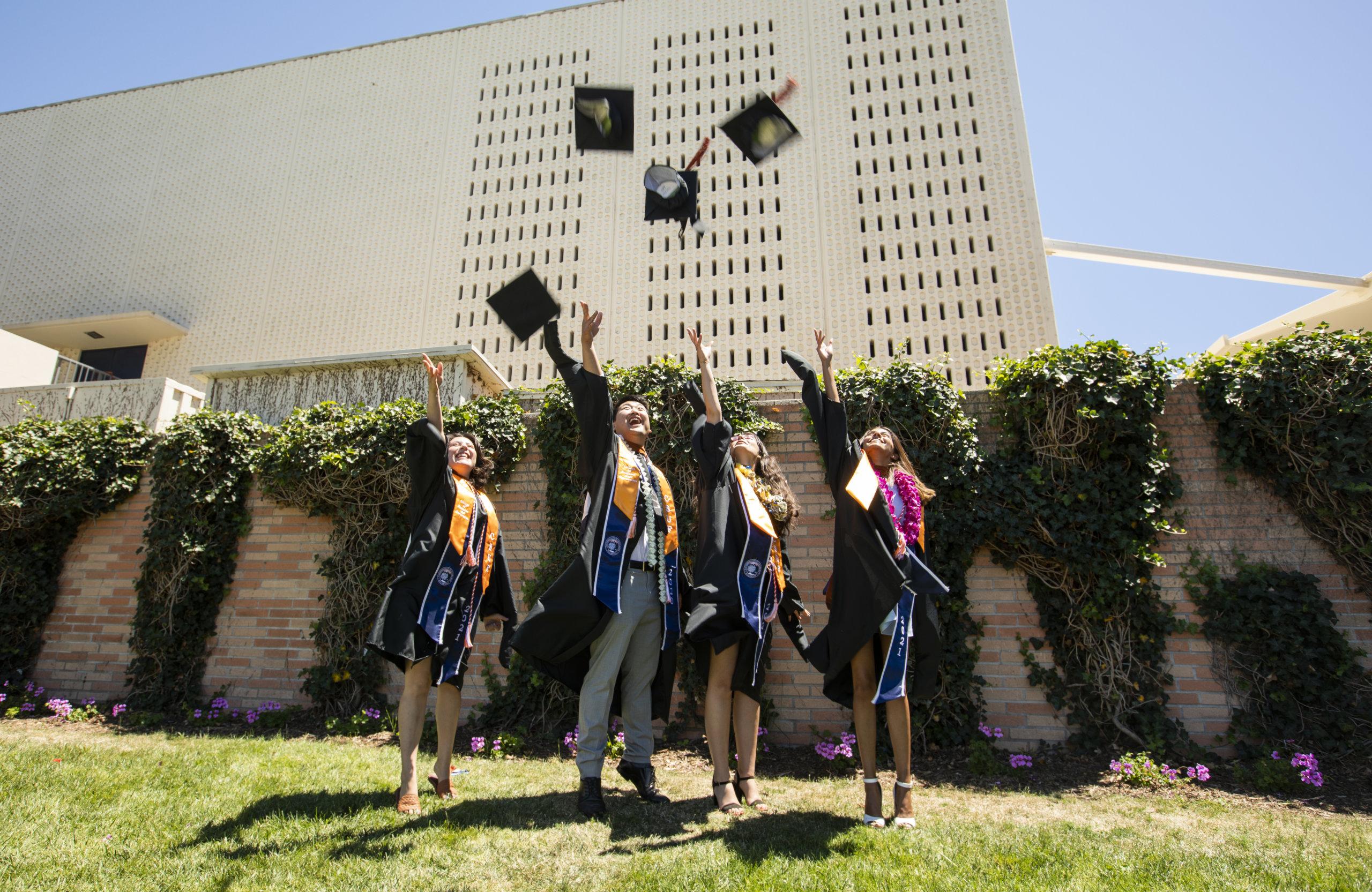 Four graduates throw their caps