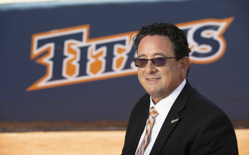man wearing a dark suit, orange and white tie and sunglasses