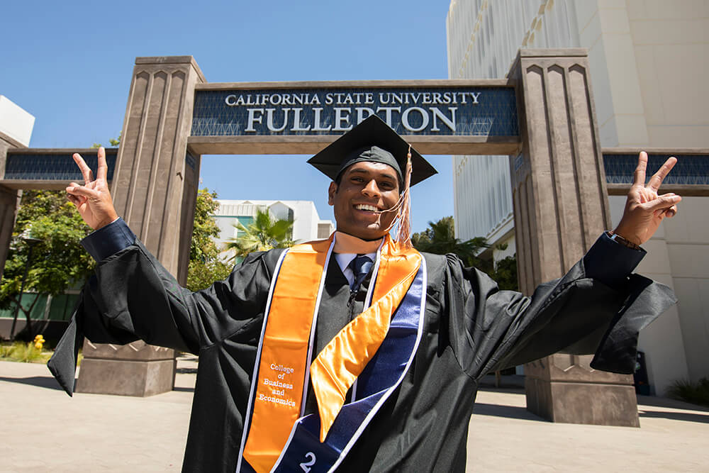 Happy graduate at campus entrance