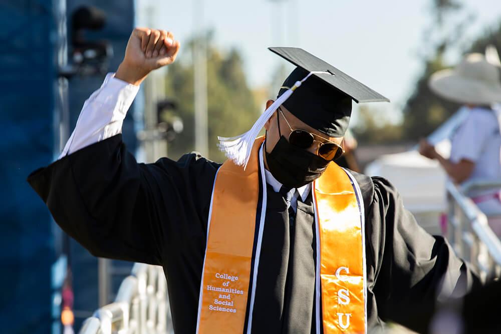 Graduate raises fist in air in celebration