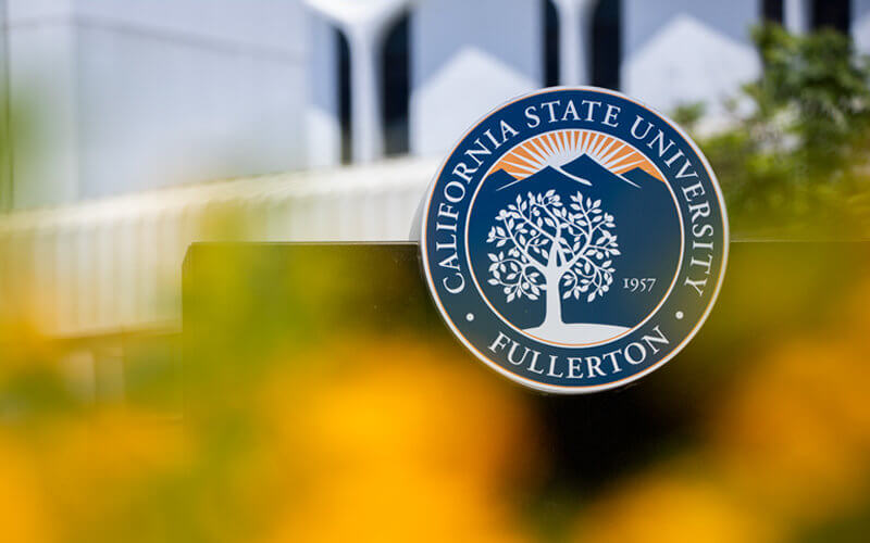 CSUF Seal framed by flowers and McCarthy Hall