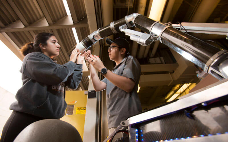 Dana Castro and Ternel Enriquez conduct student research on the Titan Rover project.