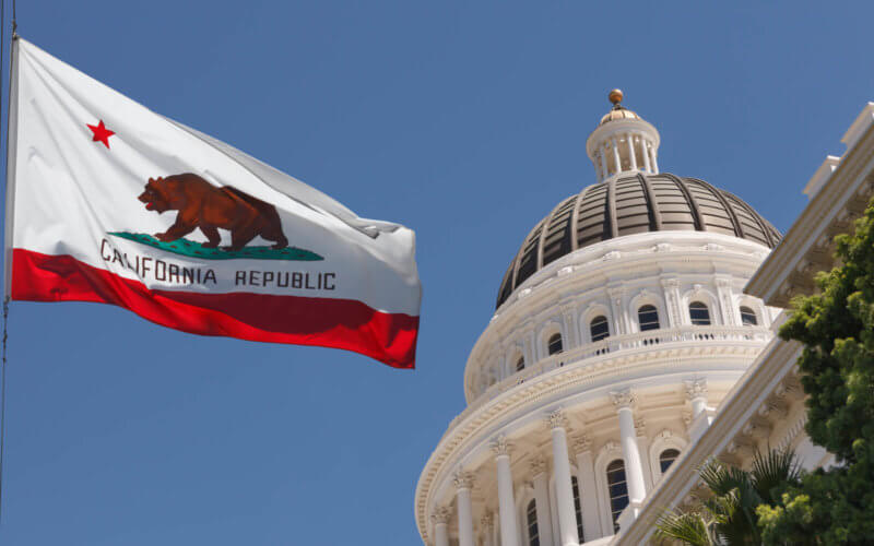California state flag with capitol building in background